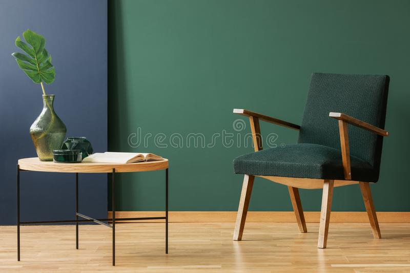 Wooden armchair next to table and book in green and blue living room interior. Real photo. Wooden armchair next to table with leaf and book in green and blue stock photography