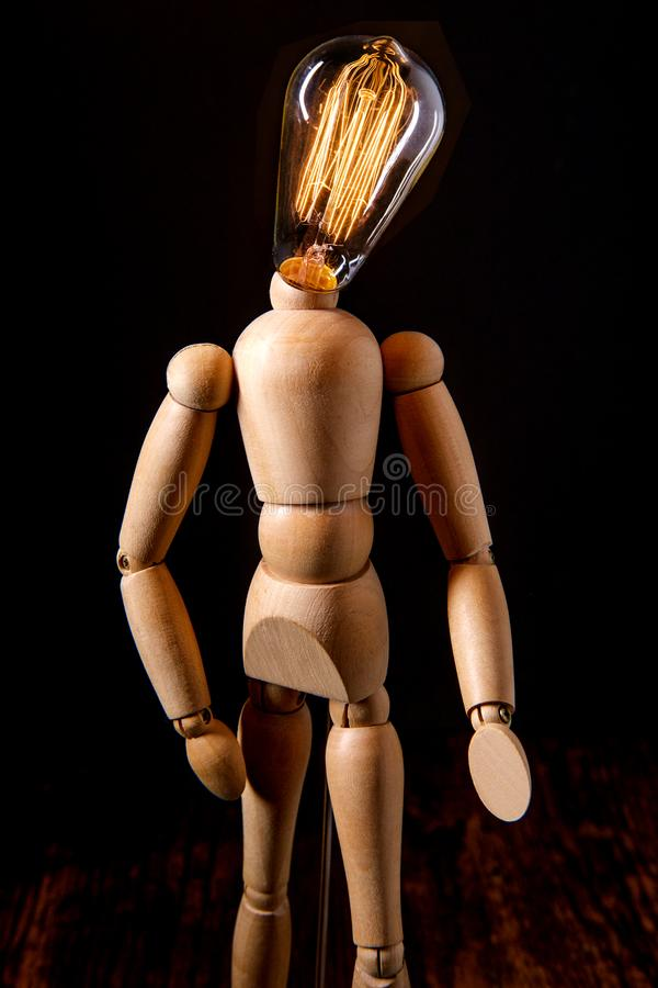 Wooden Art Doll Lightbulb. Wooden articulated artist doll with antique edison light bulb for a head symbolizing creativity royalty free stock image