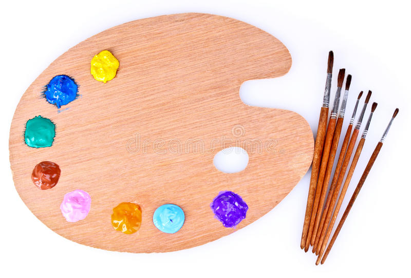 Wooden art palette of paint and brush royalty free stock images