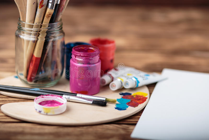 Wooden art palette with tubes of oil paints and a brush. Art and craft tools. Artist`s brush, canvas, palette knife. Space for tex royalty free stock photography