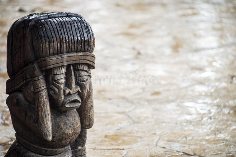 Wooden Aztec sculpture. A wooden Aztec sculpture with concerned look on its face near a road in the rain royalty free stock photography