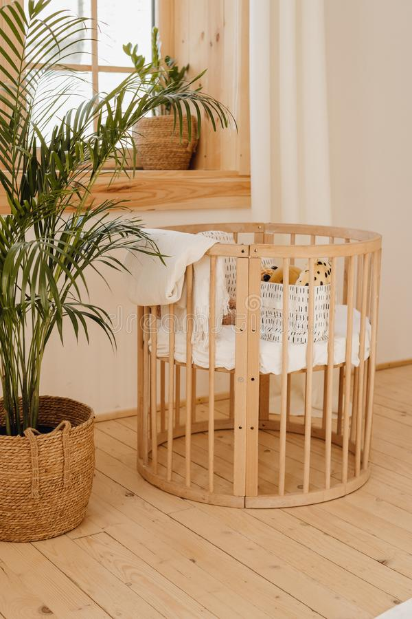 Wooden Baby Bed Crib in Eco Friendly Cozy Interior royalty free stock image