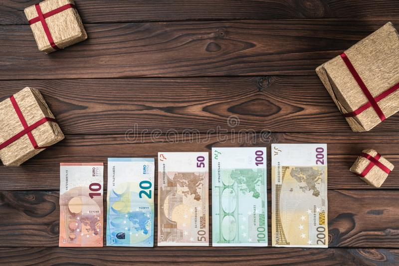 Wooden background. European money and gifts of different value. Space for text. Top view stock image