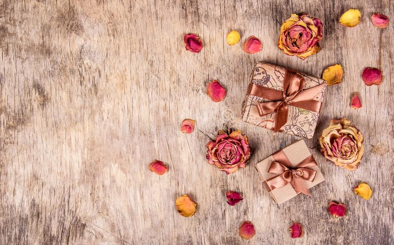 Wooden background with gift and roses. Dry flowers, dried roses. royalty free stock image