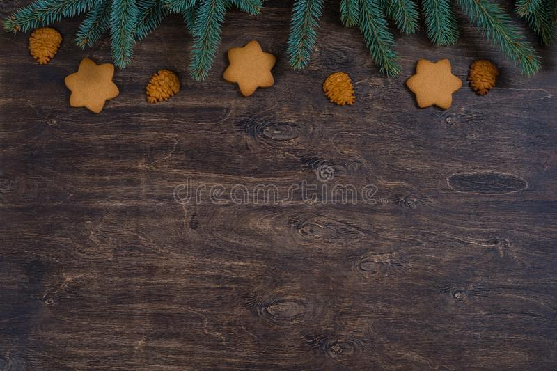 Background with gingerbread Christmas cookies and fir-tree branches royalty free stock photos