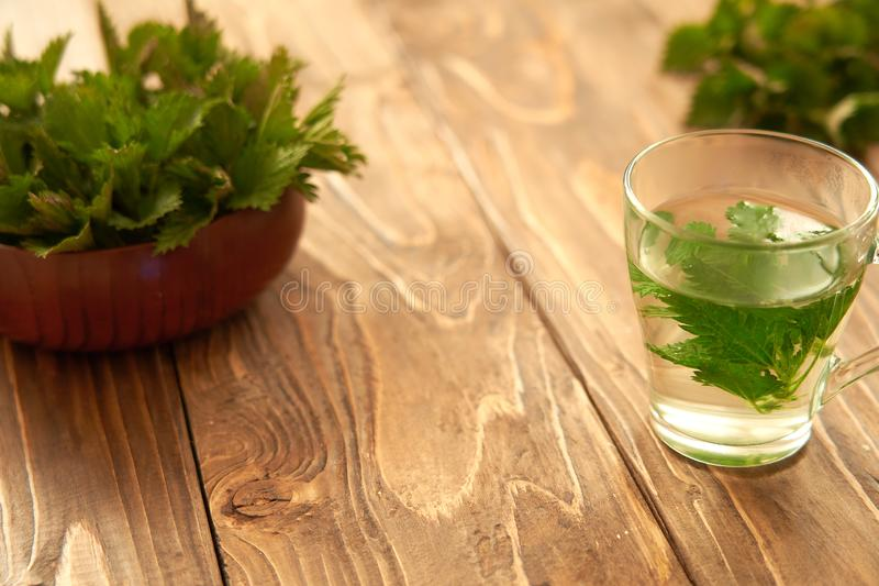 On a wooden background is a glass with brewed young nettles. medicinal broth of nettle. vitamin herbal tea stock photos