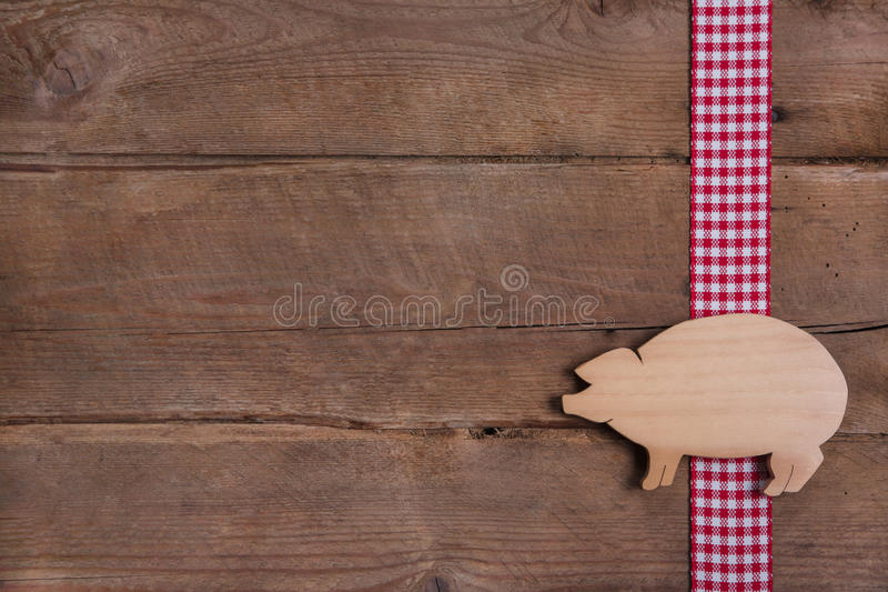 Wooden background with good luck pig on checkered ribbon stock images