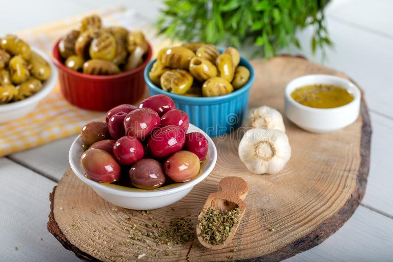 Wooden background with green olives, olive oil, garlic and spices royalty free stock image