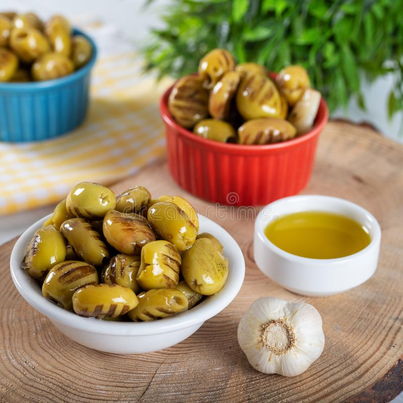 Wooden background with green olives, olive oil, garlic and spices royalty free stock photo