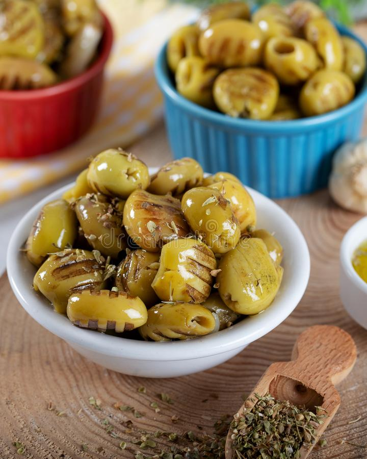 Wooden background with green olives, olive oil, garlic and spices royalty free stock photography