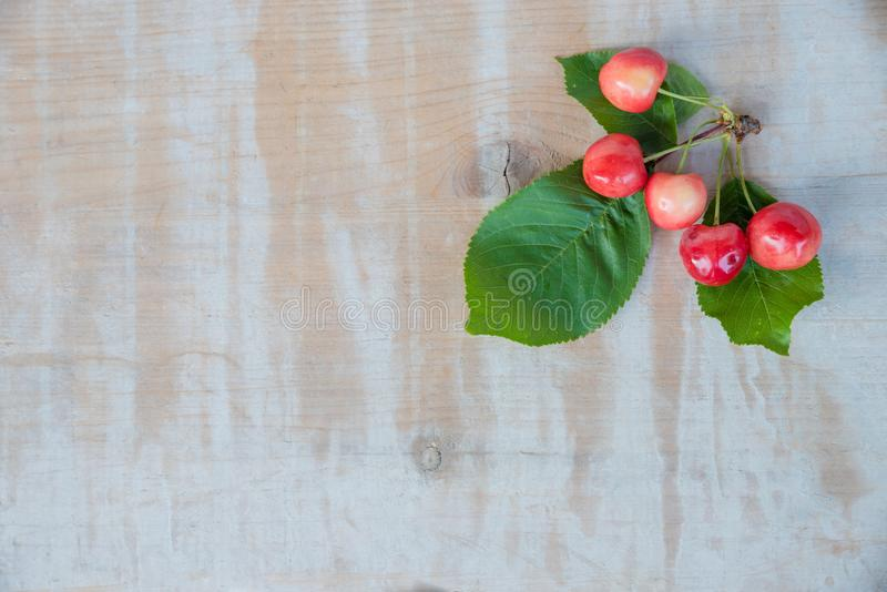 Wooden background with group of cherry fruits and green leaves royalty free stock photo