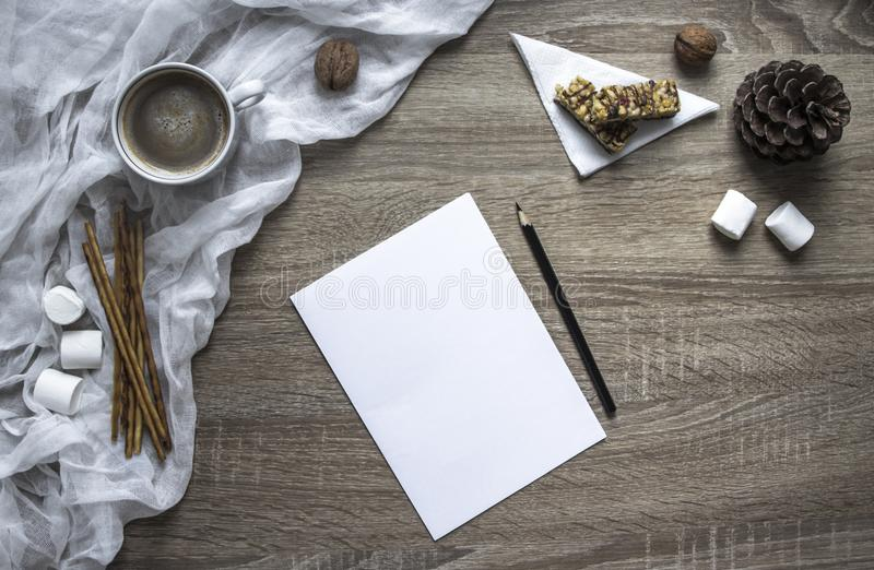 On a wooden background a leaf and a pen write marshmallows and sweets, a mug with cocoa lies a melted snowman made of marshmallow stock photography