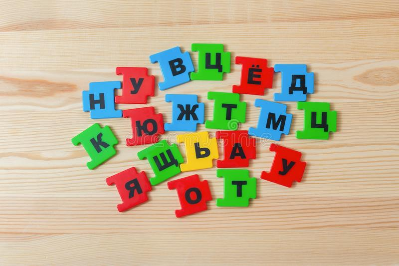 On a wooden background lies a group of letters of the Russian alphabet stock photo