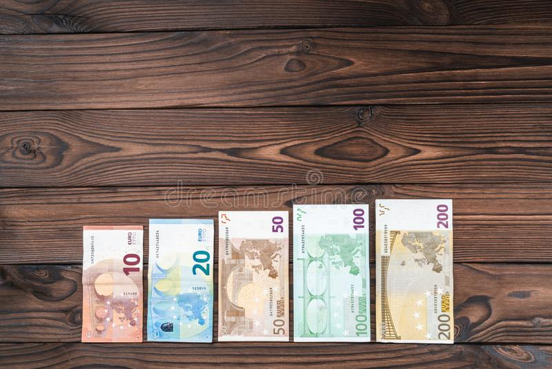 Wooden background, money of different value, steps in career growth, salary per hour. Top view stock photos
