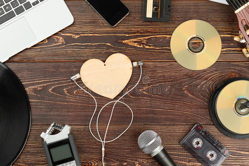 Wooden background with outdated and modern musical technology. royalty free stock photography