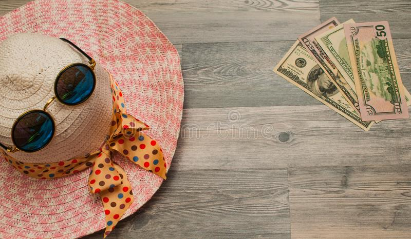 On a wooden background, panama from the sun with eyeglasses and money for entertainment. royalty free stock images