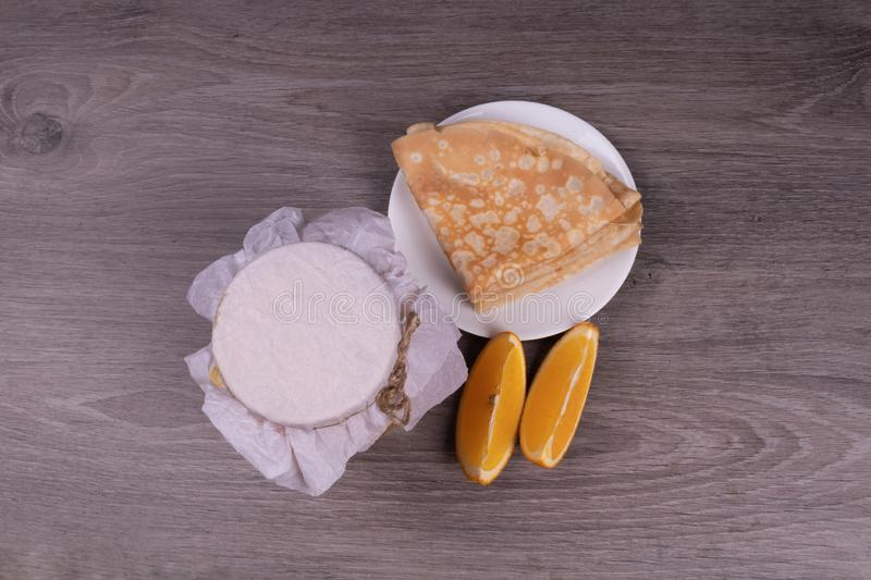 On a wooden background a plate with pancakes, a jar under a paper lid of a lemon wedge view from the top stock photo