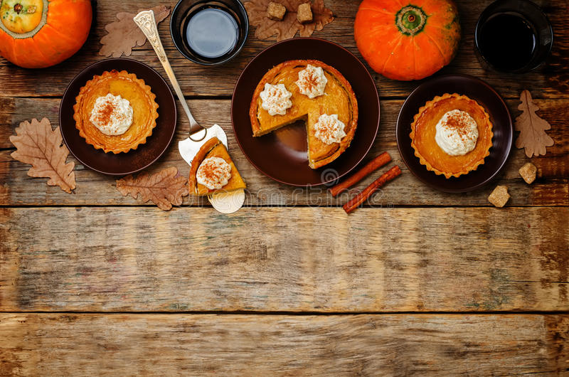 Wooden background with pumpkin pies, pumpkin and coffee. Autumn stock image