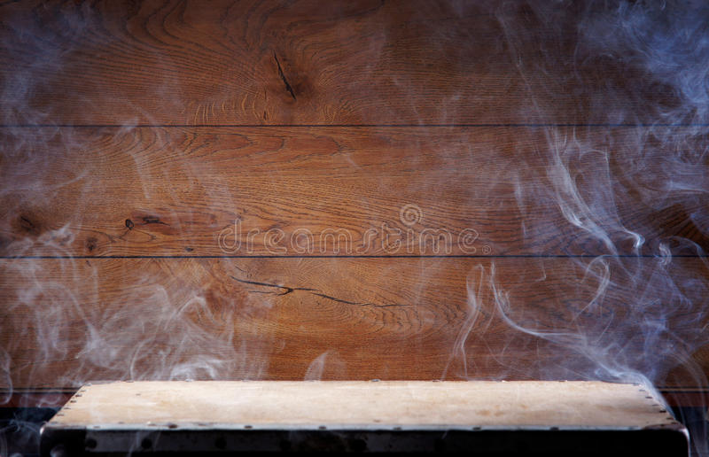A wooden background and a table covered with smoke stock photos