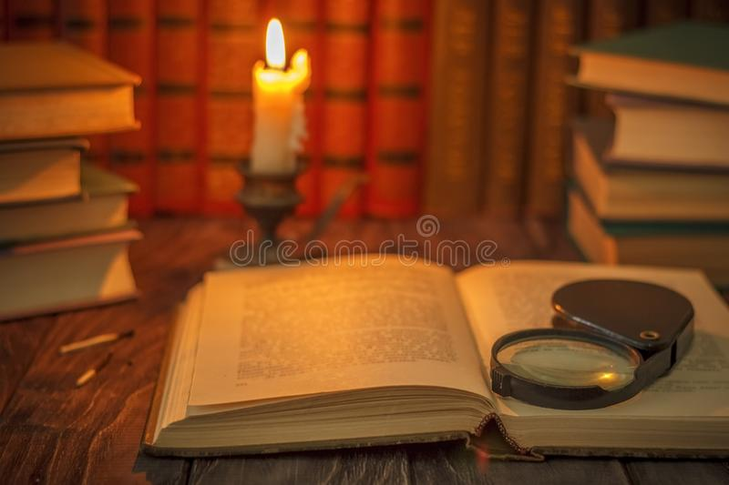 On the wooden background of the table there are stacks of colorful books near the old candlestick with burnt matches lying next t stock photos