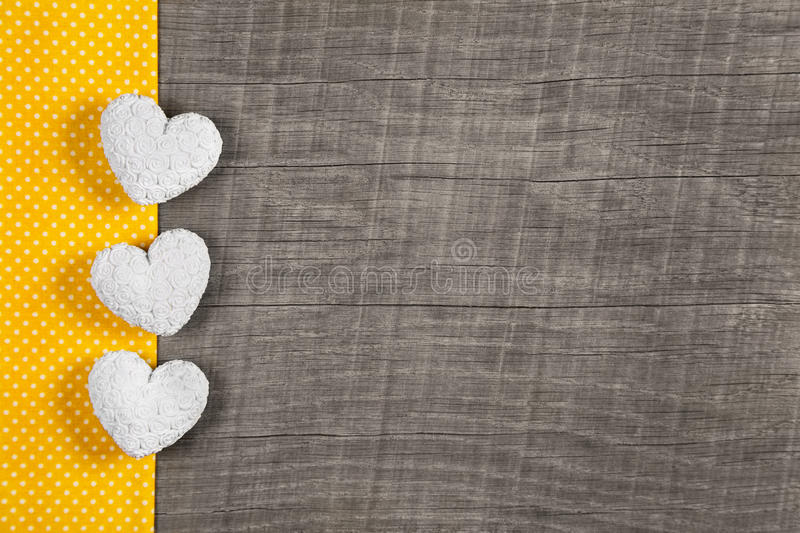 Wooden background with three white and yellow hearts on wooden b stock photo