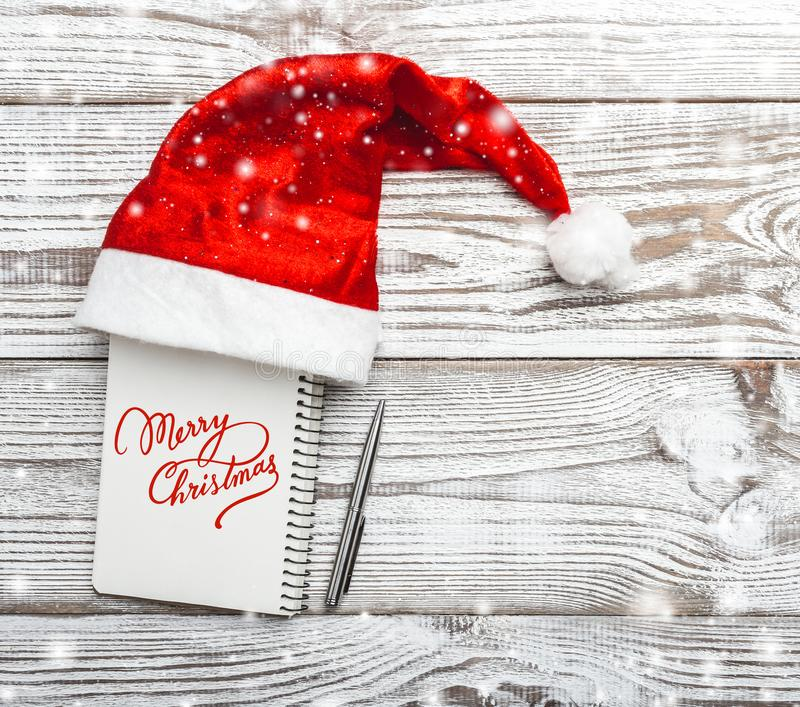 Wooden background. White. Winter card. His Santa`s hat. Xmas card. Letter for a Christmas or New Year greeting card. With the ins stock photos
