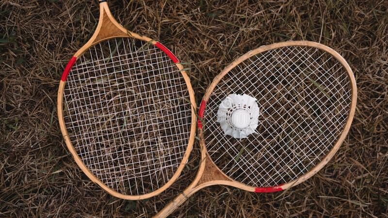 Wooden badminton rackets and a white feather shuttlecock. The game of badminton. Hobbies and outdoor recreation royalty free stock photo
