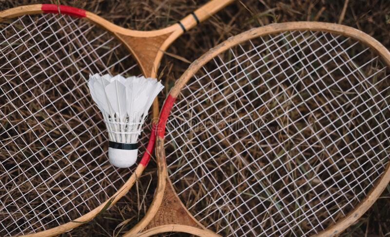 Wooden badminton rackets and a white feather shuttlecock. The game of badminton. Hobbies and outdoor recreation stock photography