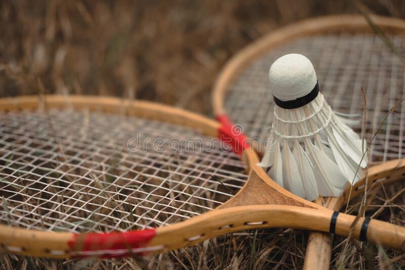 Wooden badminton rackets and a white feather shuttlecock. The game of badminton. Hobbies and outdoor recreation royalty free stock photos