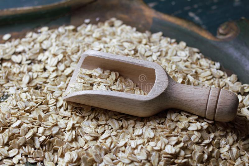 Wooden bailer with oat flakes. Bailer with oat flakes on the green background royalty free stock photo