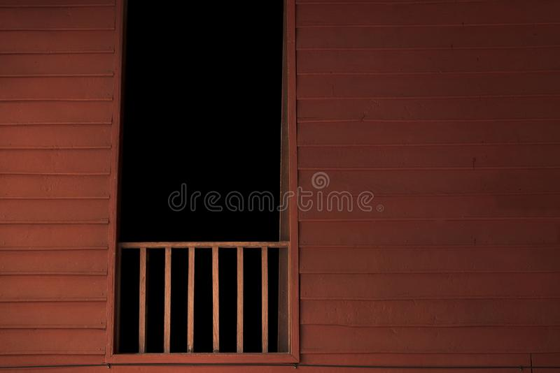 Wooden balcony with dark room in window. Thai style house. Haunted house background concept stock image