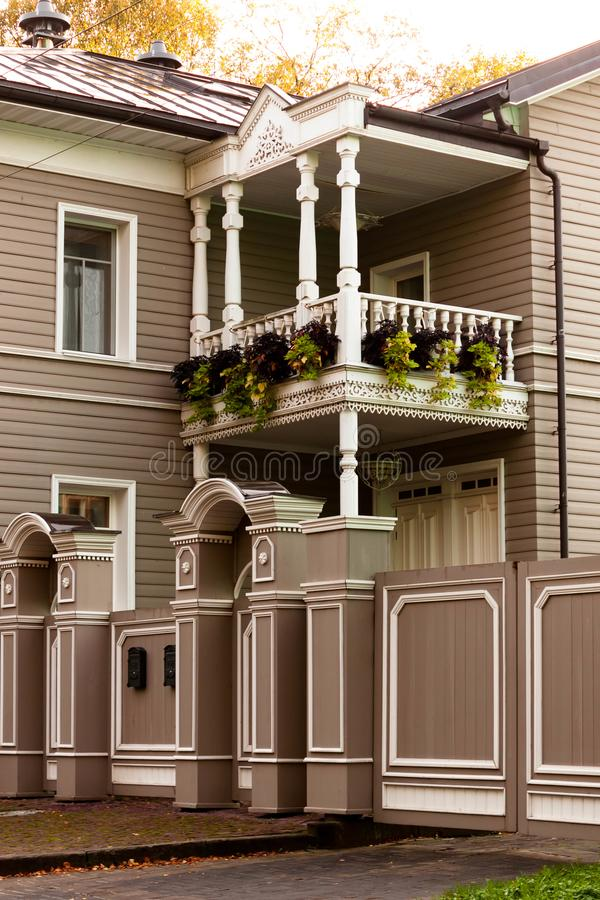 Wooden balcony in a wooden house in Vologda, Russia with plants on 2nd floor with white carving trim. Wooden balcony in a wooden house in Vologda, Russia with stock images
