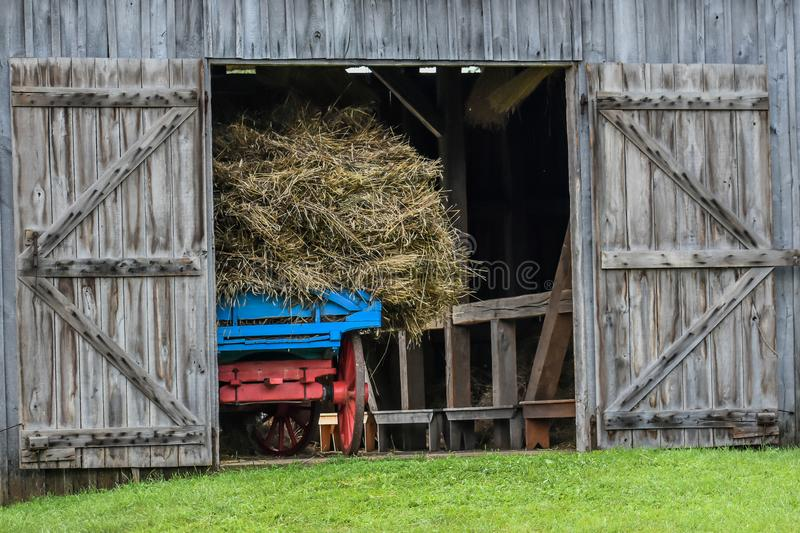 Wooden Barn with a Carriage full of Hay stock photography