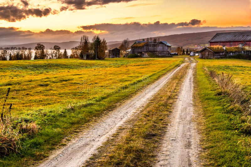 Wooden barn with farmhouse at sunset in Norway stock photo