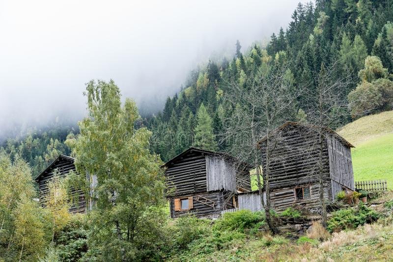 A wooden barn on the hill surrounded by fir forest. Old cottage on the mountain inside the cloud, natural environment. Hiking in the alps, Tirol, Austria royalty free stock image