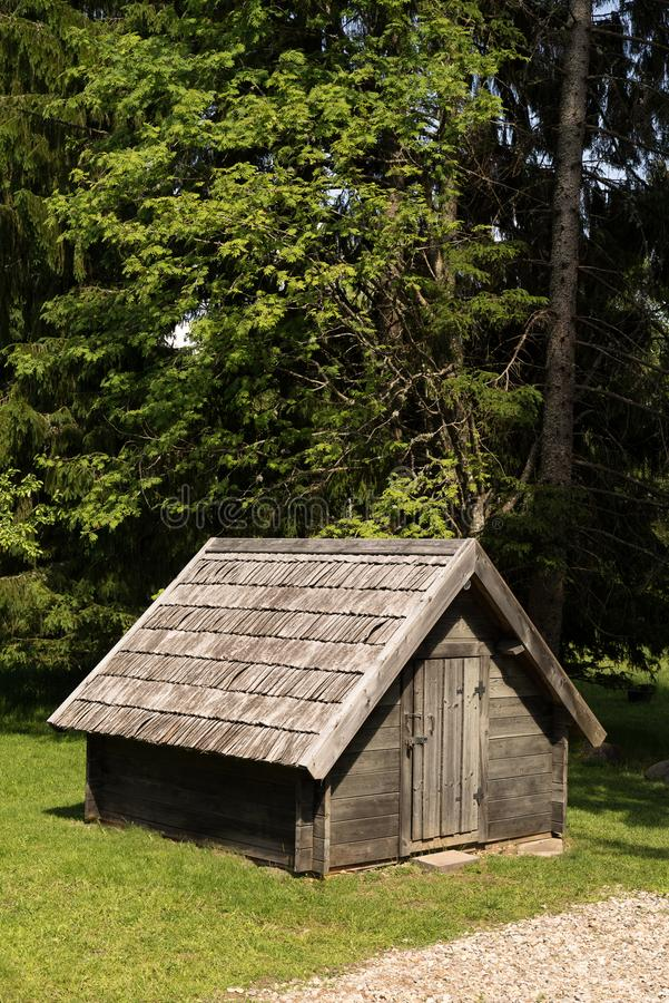 A wooden barn surrounded by mixed forest. Old cottage on green environment background. A wooden barn surrounded by mixed forest. Old cottage on green stock images