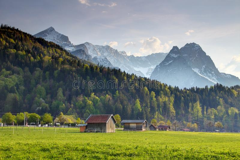 Wooden barns in meadow with jagged Alpspitze, Zugspitze peaks. Old timber hay barns in sunny pasture in German country in springtime with snowy Alpspitze stock photo