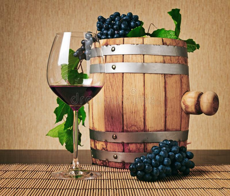 Wooden barrel and glass of red wine on table. Wooden wine barrel, glass of red wine and bunches of ripe grape on table. Eco winemaking product. Classical stock photography