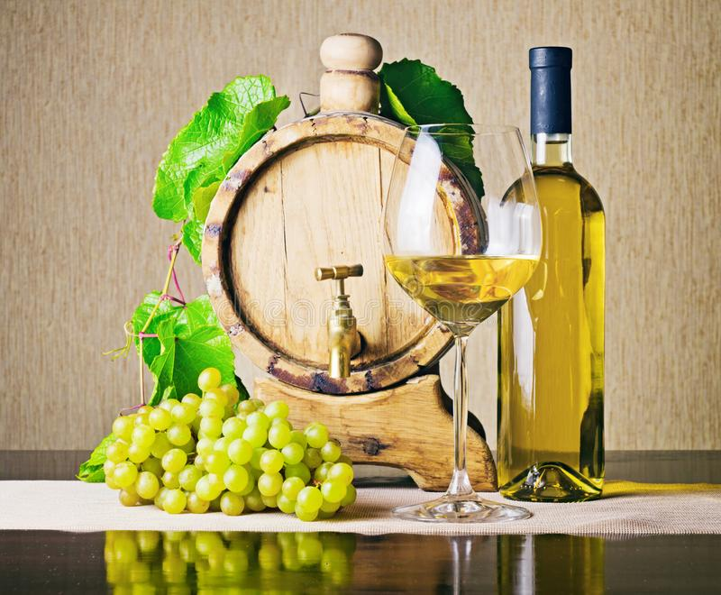 Wooden barrel with grape twig and bottle of white wine. Wooden wine barrel with grape twig, bottle of white wine, wine glass and bunch of ripe grape on table stock photos