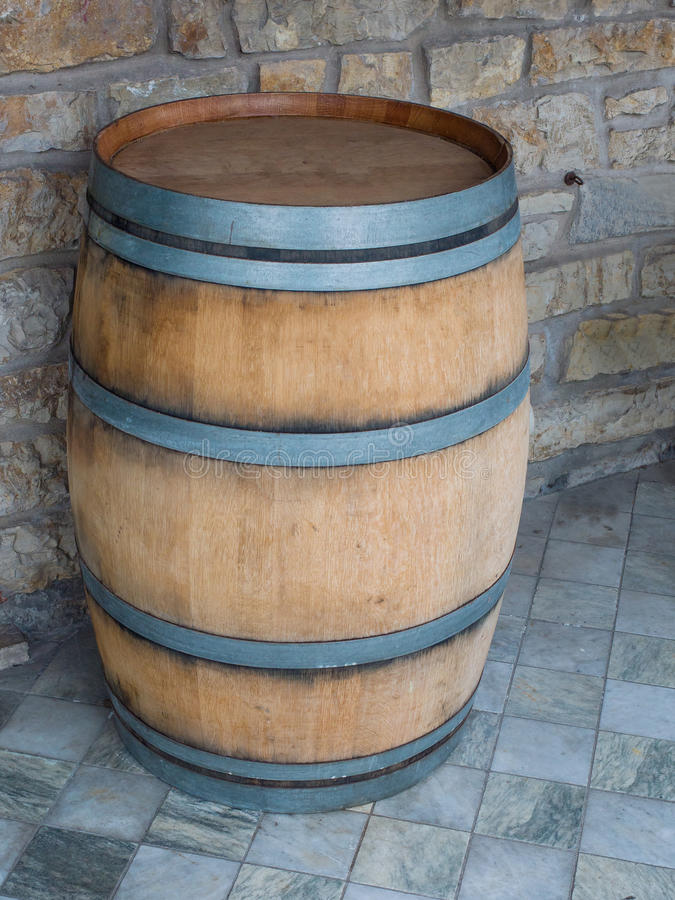 Wooden barrel on marble tile floor, stone wall in background. Wooden barrel with iron rings on a marble tile floor, rough stone wall in background royalty free stock photos