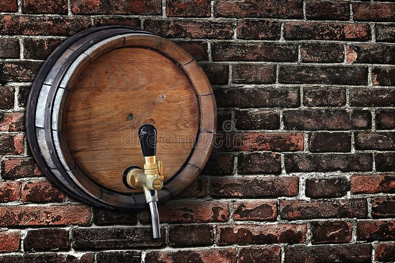Wooden barrel with a tap in the old brick wall in grunge style royalty free stock photos