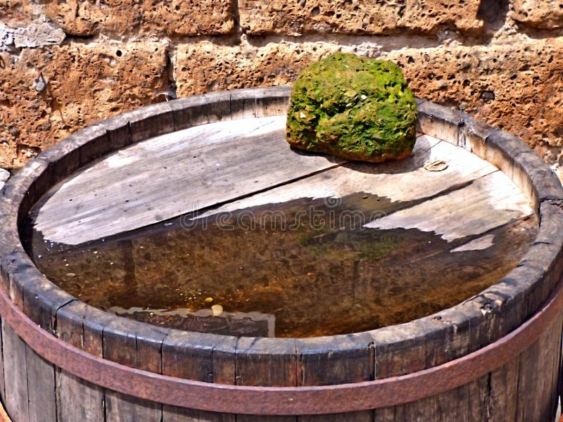 Wooden barrel with a water puddle and a mossy rock. Closeup of a mossy rock on a wooden barrel beside a puddle of water from a recent rain. With a stone wall stock photos