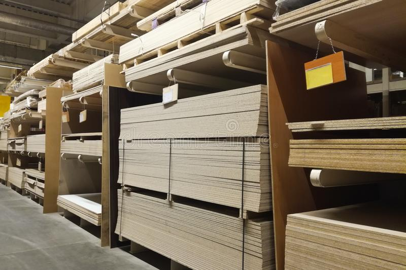 wooden bars at lumber yard of hardware store. Rack of pre-cut panel, mill wood timber, siding, plywood in warehouse royalty free stock image
