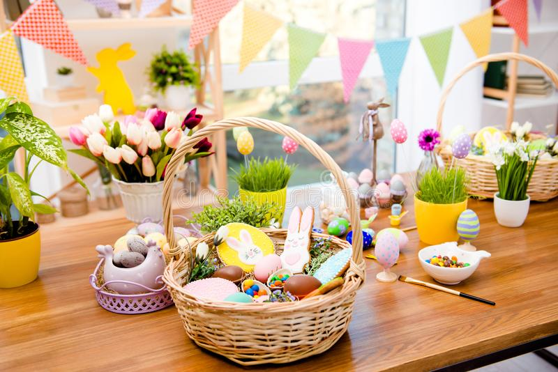 Wooden basket with easter composition, sweets, choco, gingerbread standing on table decorated with easter colored eggs and flowers royalty free stock image