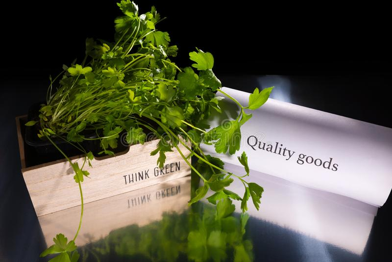 Wooden basket with green plant/parsley  is on the transparent table/background. The basket has note `Think green`. Near the basket. Is the note `Quality goods royalty free stock image