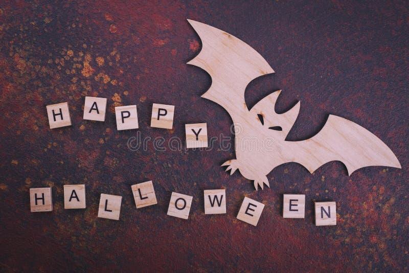 Wooden bat, text Happy Halloween stock photography
