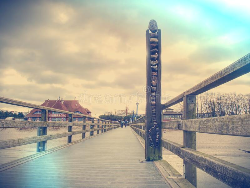 Wooden batten bridge juts out into the sea royalty free stock images