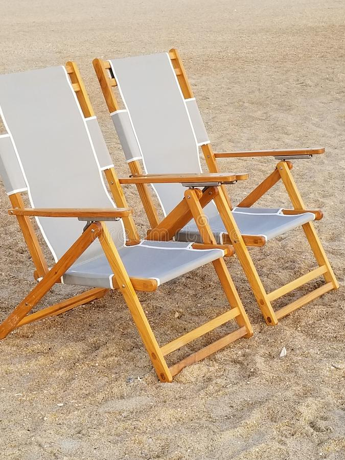 Wooden beach chairs on sand. Ocean stock images