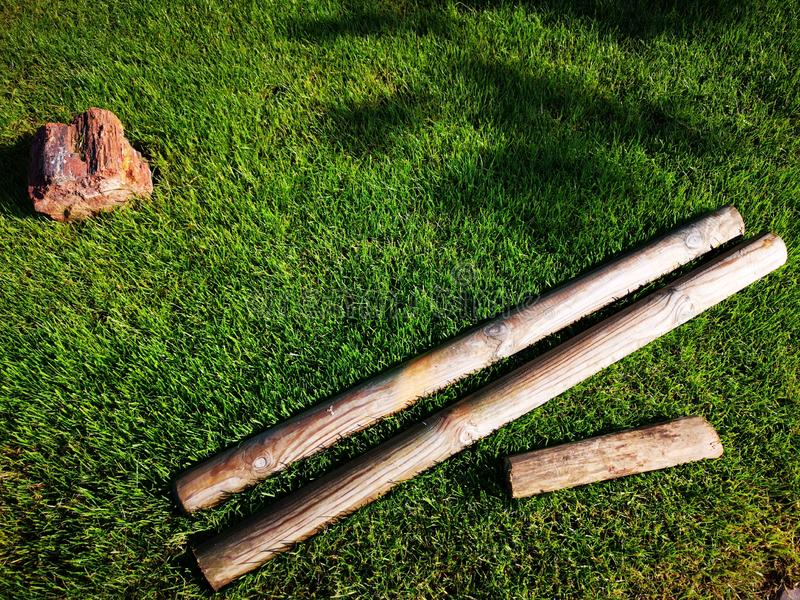 Wooden beams and a piece of mineral rock on the grass. Wooden beams and a little piece of mineral rock on the grass. Natural decorative composition with stone stock images