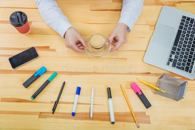 Wooden beautiful table. It has a laptop, a feather, markers, a coffee cup, pencil, phone ,a gray laptop and a women`s. Wooden beautiful table. It has a laptop, a stock photo